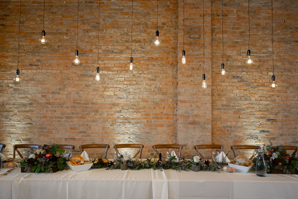 A head table with exposed brick walls in the background and industrial lights hanging from the ceiling.