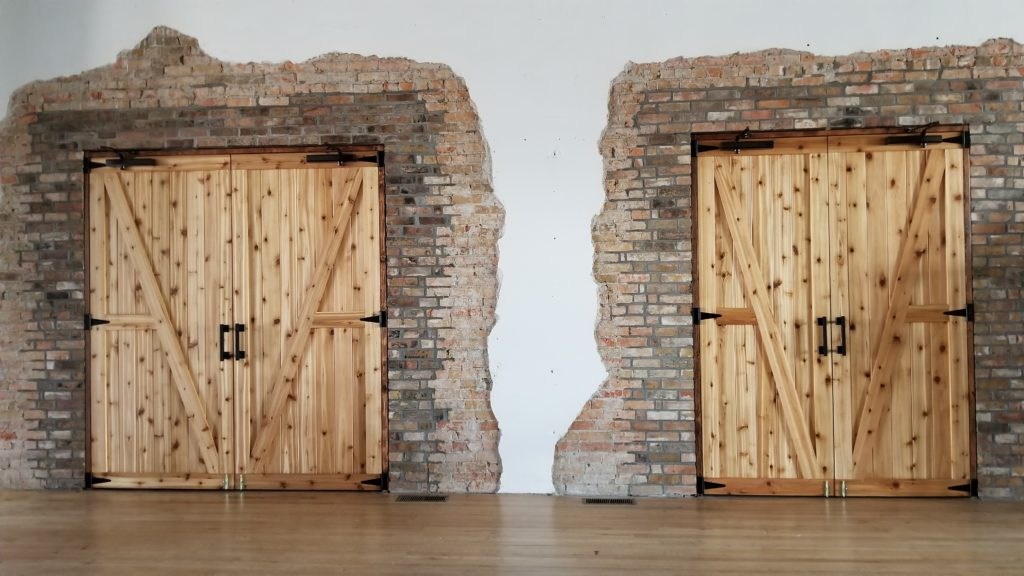 Handcrafted barn-style doors and exposed brick are found in the Stein Room.